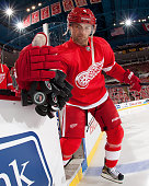 Jakub Kindl of the Detroit Red Wings scoops the pucks onto the ice for warmups before an NHL game against the Tampa Bay Lightning at Joe Louis Arena...