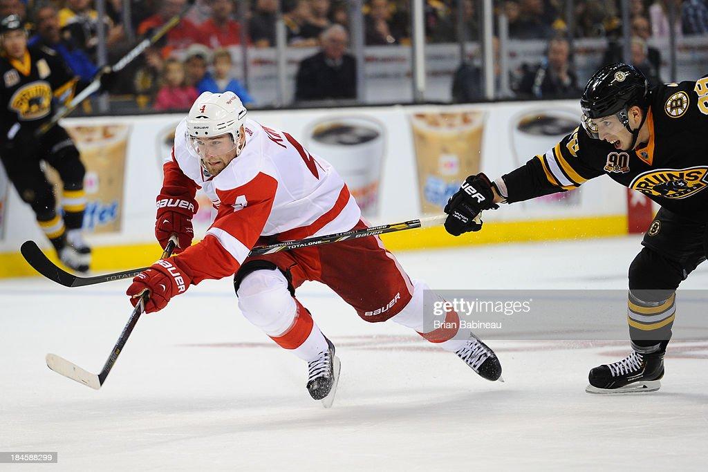 Jakub Kindl #4 of the Detroit Red Wings skates against Jordan Caron #38 of the Boston Bruins at the TD Garden on October 14, 2013 in Boston, Massachusetts.