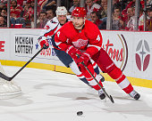 Jakub Kindl of the Detroit Red Wings skates around the net with the puck in front of Jason Chimera of the Washington Capitals during an NHL game at...