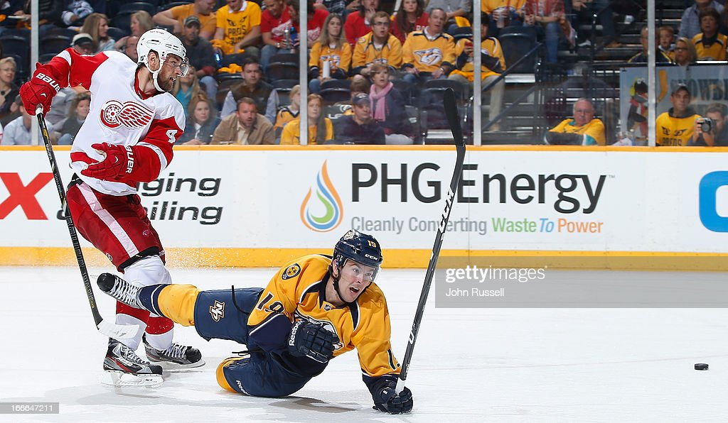 Jakub Kindl #4 of the Detroit Red Wings takes Bobby Butler #19 of the Nashville Predators to the ice on a breakaway during an NHL game at the Bridgestone Arena on April 14, 2013 in Nashville, Tennessee.