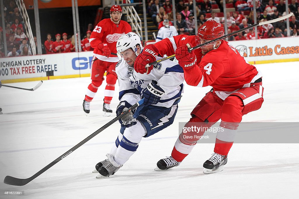 <a gi-track='captionPersonalityLinkClicked' href=/galleries/search?phrase=Jakub+Kindl&family=editorial&specificpeople=716743 ng-click='$event.stopPropagation()'>Jakub Kindl</a> #4 of the Detroit Red Wings tries to body <a gi-track='captionPersonalityLinkClicked' href=/galleries/search?phrase=Tyler+Johnson+-+Ice+Hockey+Player&family=editorial&specificpeople=14574766 ng-click='$event.stopPropagation()'>Tyler Johnson</a> #9 of the Tampa Bay Lightning off the puck during an NHL game on March 30, 2014 at Joe Louis Arena in Detroit, Michigan.