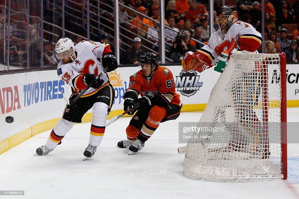 Jakub Nakladal #33 of the Calgary Flames passes the puck as Rickard Rakell #67 of the Anaheim Ducks defends while Jonas Hiller #1 of the Calgary Flames looks on during the third period of a game at Honda Center on February 21, 2016 in Anaheim, California.