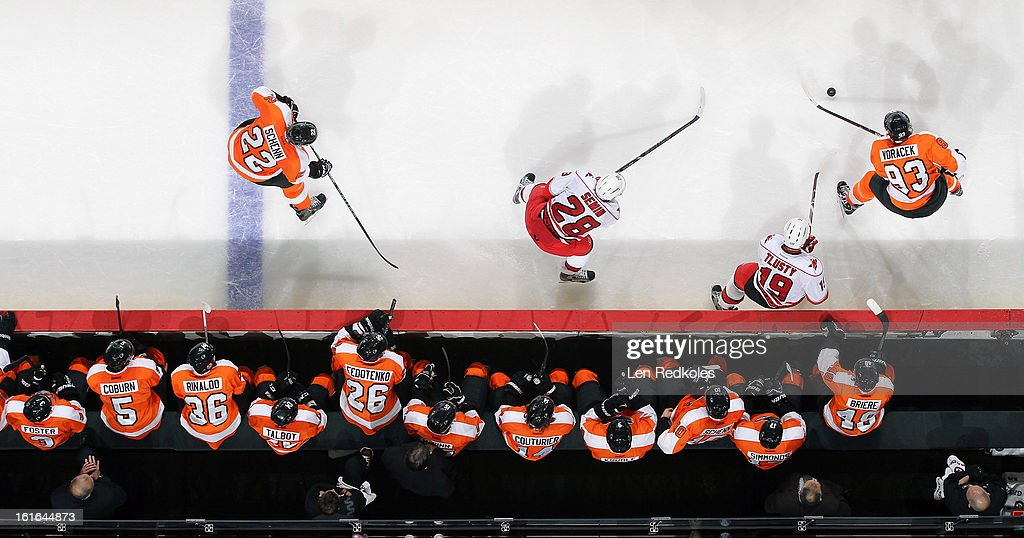 Jakub Voracek #93 looks to pass the puck to Luke Schenn #22 of the Philadelphia Flyers as they skate in front of the bench against Alexander Semin #28 and Jiri Tlusty #19 of the Carolina Hurricanes on February 9, 2013 at the Wells Fargo Center in Philadelphia, Pennsylvania.