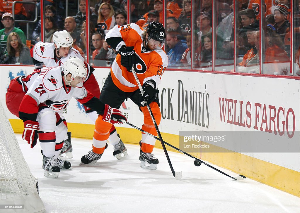 Jakub Voracek #93 of the Philadelphia Flyers battles for the puck against Bobby Sanguinetti #24 and Eric Staal #12 of the Carolina Hurricanes on February 9, 2013 at the Wells Fargo Center in Philadelphia, Pennsylvania.