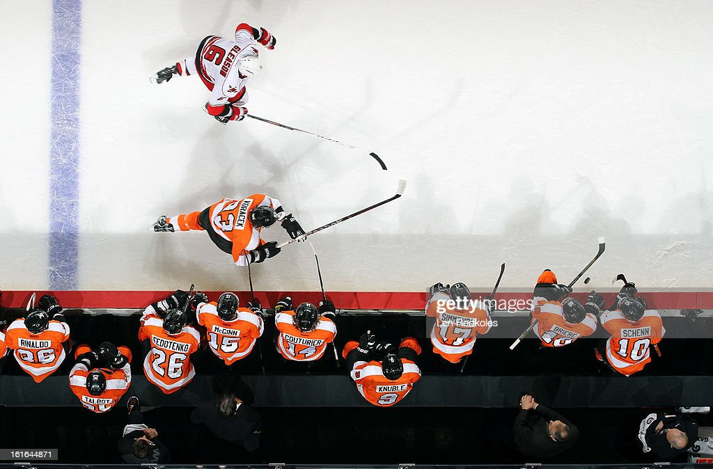Jakub Voracek #93 of the Philadelphia Flyers skates after the loose puck in front of the bench against Tim Gleason #6 of the Carolina Hurricanes on February 9, 2013 at the Wells Fargo Center in Philadelphia, Pennsylvania.