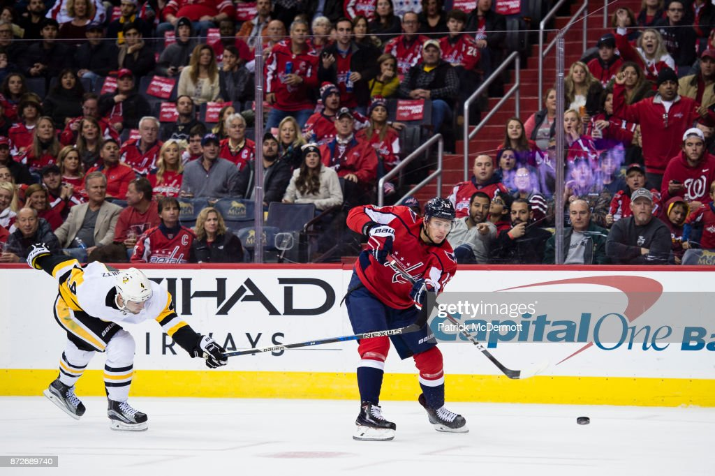 Jakub Vrana #13 of the Washington Capitals shoots and scores an empty net goal against Justin Schultz #4 of the Pittsburgh Penguins in the third period at Capital One Arena on November 10, 2017 in Washington, DC.