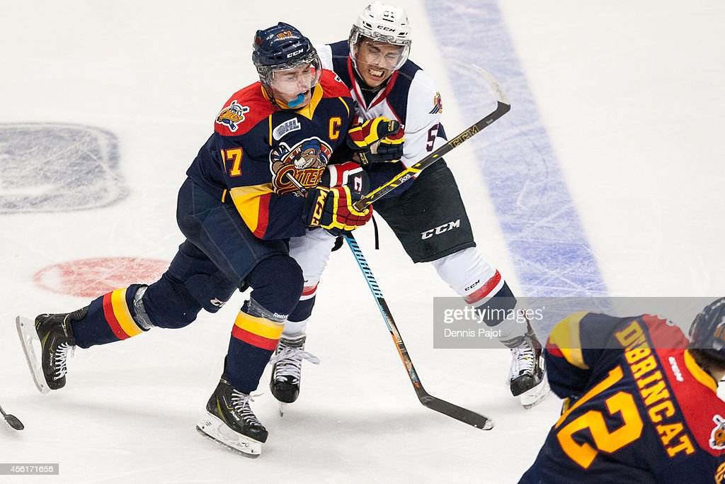 Jalen Chatfield #51 of the Windsor Spitfires places a huge mid ice hit on <a gi-track='captionPersonalityLinkClicked' href=/galleries/search?phrase=Connor+McDavid&family=editorial&specificpeople=9756794 ng-click='$event.stopPropagation()'>Connor McDavid</a> #97 of the Erie Otters on September 26, 2014 at the WFCU Centre in Windsor, Ontario, Canada.