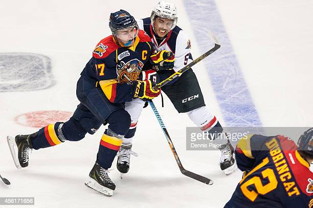 Jalen Chatfield of the Windsor Spitfires places a huge mid ice hit on Connor McDavid of the Erie Otters on September 26 2014 at the WFCU Centre in...