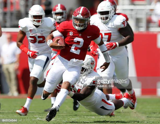 Jalen Hurts of the Alabama Crimson Tide breaks a tackle by Tobenna Okeke of the Fresno State Bulldogs at BryantDenny Stadium on September 9 2017 in...