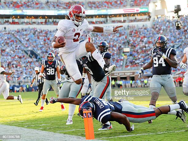Jalen Hurts of the Alabama Crimson Tide leaps over Terry Caldwell of the Mississippi Rebels at VaughtHemingway Stadium on September 17 2016 in Oxford...