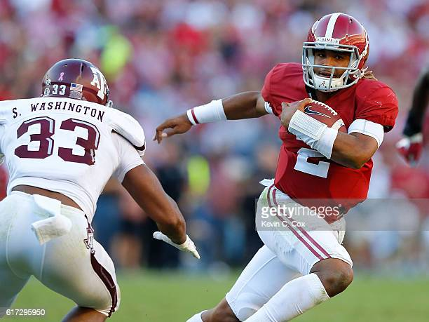 Jalen Hurts of the Alabama Crimson Tide rushes away from Shaan Washington of the Texas AM Aggies at BryantDenny Stadium on October 22 2016 in...