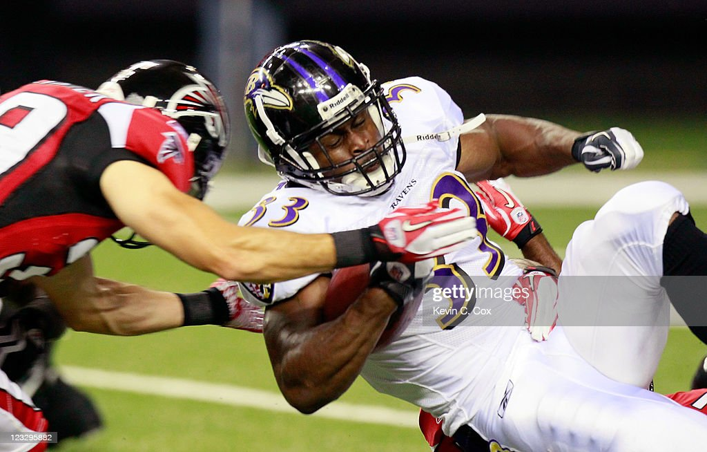 Jalen Parmele #33 of the Baltimore Ravens is tackled by Shann Schillinger #39 of the Atlanta Falcons at Georgia Dome on September 1, 2011 in Atlanta, Georgia.