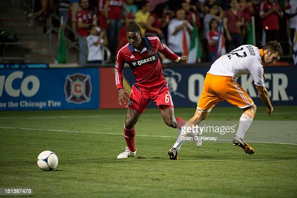 Jalil Anibaba of Chicago Fire trips up Will Bruin of Houston Dynamo at Toyota Park on September 2 2012 in Bridgeview Illinois The Fire defeated the...