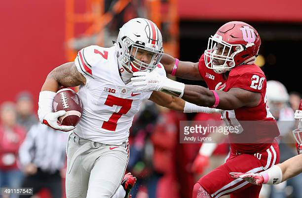Jalin Marshall of the Ohio State Buckeyes runs with the ball while defended by Jameel Cook Jr of the Indiana Hoosiers at Memorial Stadium on October...
