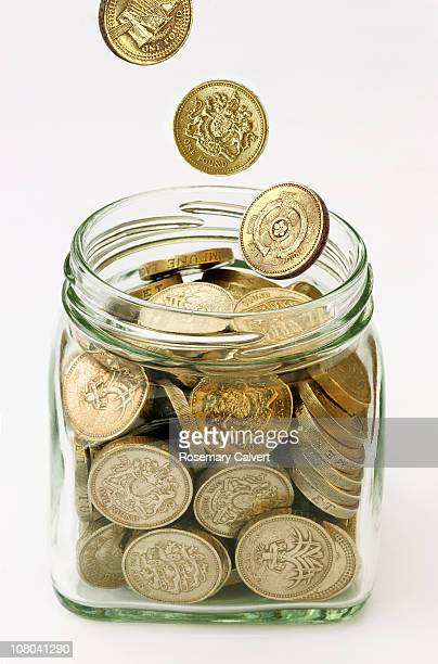 Jam jar full of coins with more being added.