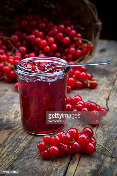 Jam jar of currant jelly and red currants, Ribes rubrum, on wooden table