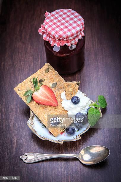 Jam jar, slice of crispbread, curd and fruits on wood