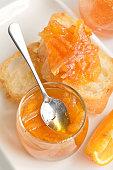Orange, jam and a crisp toast on a white background