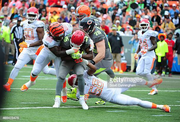 Jamaal Charles of the Kansas City Chiefs and Team Sanders is tackled by Derrick Johnson of the Kansas City Chiefs and Vontaze Burfict of the...