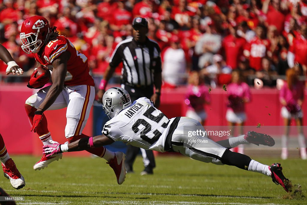 Jamaal Charles of the Kansas City Chiefs attempt to avoid the outstretched arms of DJ Hayden of the Oakland Raiders in the second quarter October 13...