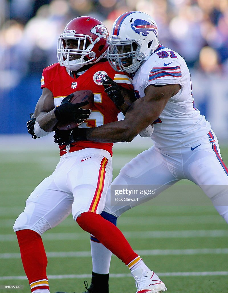 Jamaal Charles #25 of the Kansas City Chiefs is tackled by outside Manny Lawson #91 of the Buffalo Bills at Ralph Wilson Stadium on November 3, 2013 in Orchard Park, New York. Kansas City won 23-13.