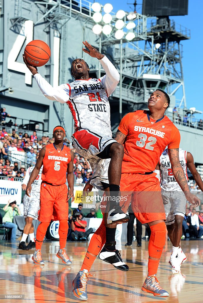 Jamaal Franklin #21 of the San Diego State Aztecs takes a foul as he attempts a shot past DaJuan Coleman #32 of the Syracuse Orange during a 62-49 Syracuse win on the USS Midway on November 11, 2012 in San Diego, California.