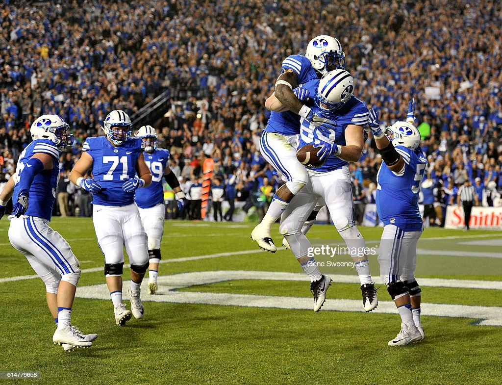 Jamaal Williams #21 of the Brigham Young Cougars celebrates with teammate Tanner Balderree #89 of the Brigham Young Cougars after Balderree scored the winning touchdown in the Cougars 28-21 double overtime win against the Mississippi State Bulldogs at LaVell Edwards Stadium on October 14, 2016 in Provo Utah.