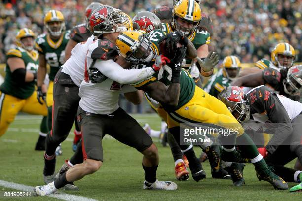 Jamaal Williams of the Green Bay Packers scores a touchdown while being tackled by Chris Conte of the Tampa Bay Buccaneers in the second quarter at...
