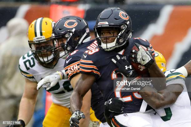 Jamaal Williams of the Green Bay Packers tackles Tarik Cohen of the Chicago Bears in the second quarter at Soldier Field on November 12 2017 in...
