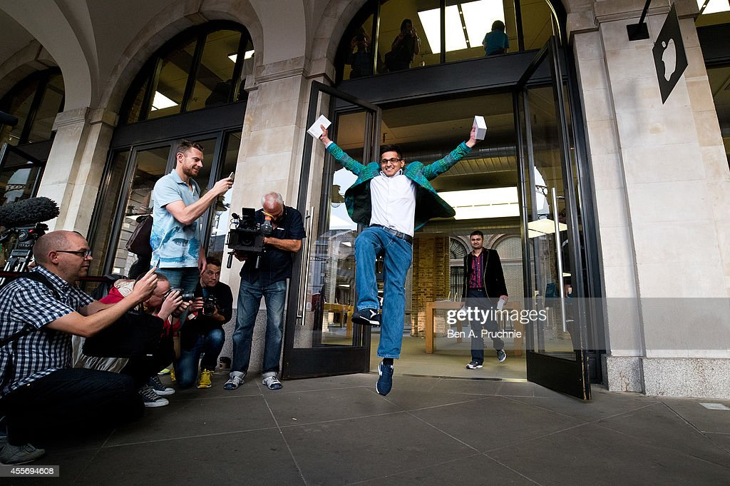 Jamael Ahmed jumps in the air as he leaves the store after being the first to purchase the iPhone 6 at Apple Covent Gardens launch on September 19...