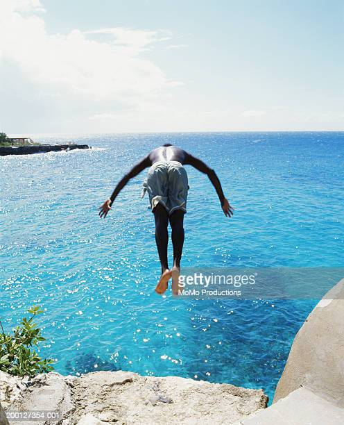 Jamaica, Negril, man diving off cliff, into ocean, rear view