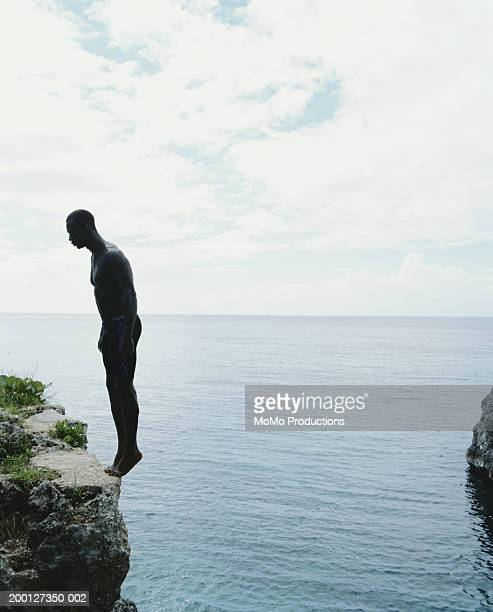Jamaica, Negril, man standing on edge of cliff, side view