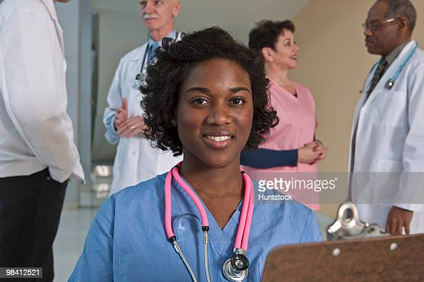 Jamaican female nurse smiling with her colleagues in the background