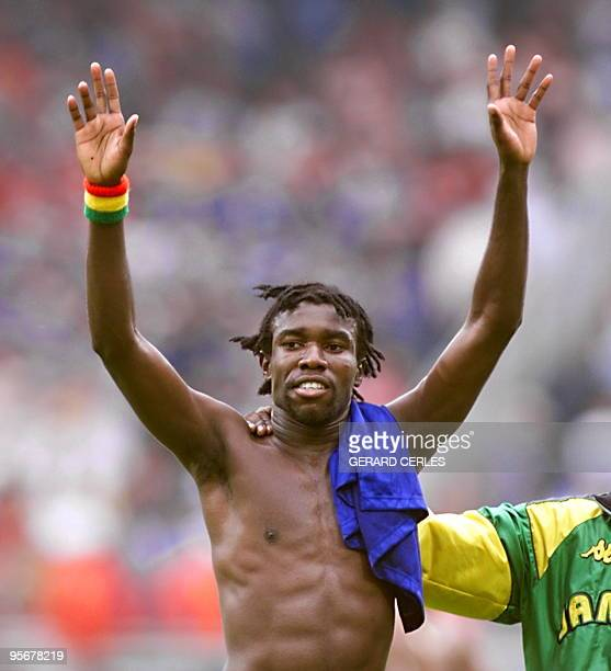 Jamaican midfielder Theodore Whitmore raises his arms in victory after winning at the Gerland stadium 26 June in Lyon central France the 1998 Soccer...