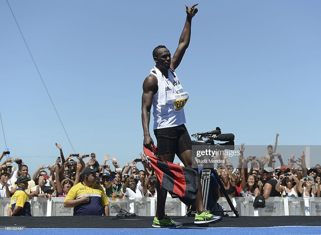Jamaican Olympic gold medallist <a gi-track='captionPersonalityLinkClicked' href=/galleries/search?phrase=Usain+Bolt&family=editorial&specificpeople=604196 ng-click='$event.stopPropagation()'>Usain Bolt</a> celebrates after winning the 'Mano a Mano' Men's 150m challenge on Copacabana beach on March 31, 2013 in Rio de Janeiro, Brazil.