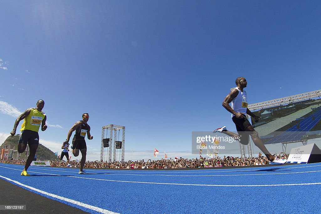 Jamaican Olympic gold medallist Usain Bolt (R) leaps ahead of Brazil's Bruno de Barros (L) and Antigua and Barbuda's Daniel Bailey (C) to win the 'Mano a Mano Men's 150 metres' challenge on Copacabana beach on March 31, 2013 in Rio de Janeiro, Brazil.