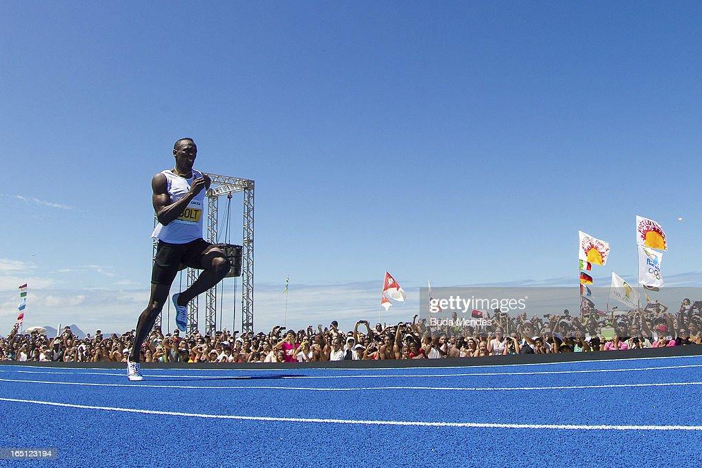 Jamaican Olympic gold medallist Usain Bolt runs to win the 'Mano a Mano' Men's 150m challenge on Copacabana beach on March 31, 2013 in Rio de Janeiro, Brazil.