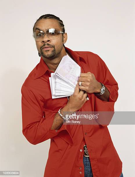 Jamaican reggae singer Shaggy pocketing a wad of fake banknotes circa 1995