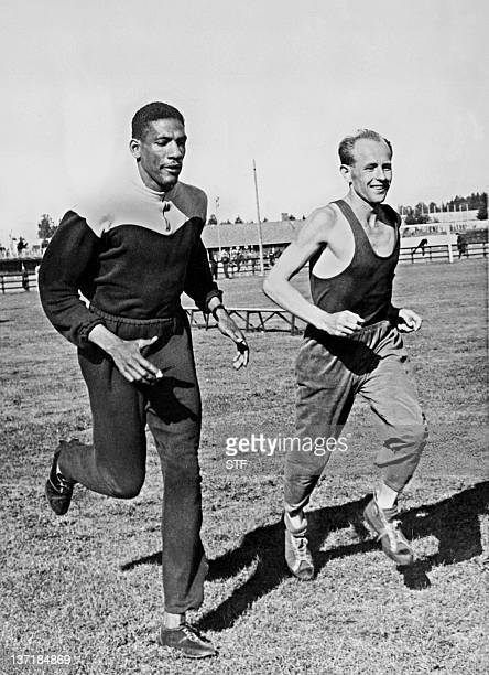 Jamaican runner Arthur Wint runs next the 'Czech locomotive' Emil Zatopek during practice 16 July 1952 in Helsinki before the start of the Olympic...