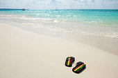 Sandals with jamaican colors on the beach of Negril during the day