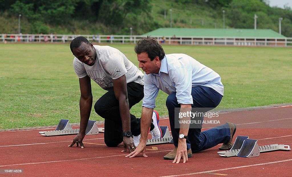 Jamaican sprinter and six-time Olympic gold medalist Usain Bolt (L) and Rio de Janeiro's Mayor Eduardo Paes get ready to race during a visit to an olympic village for children in the outskirts of Rio de Janeiro, on October 23, 2012.
