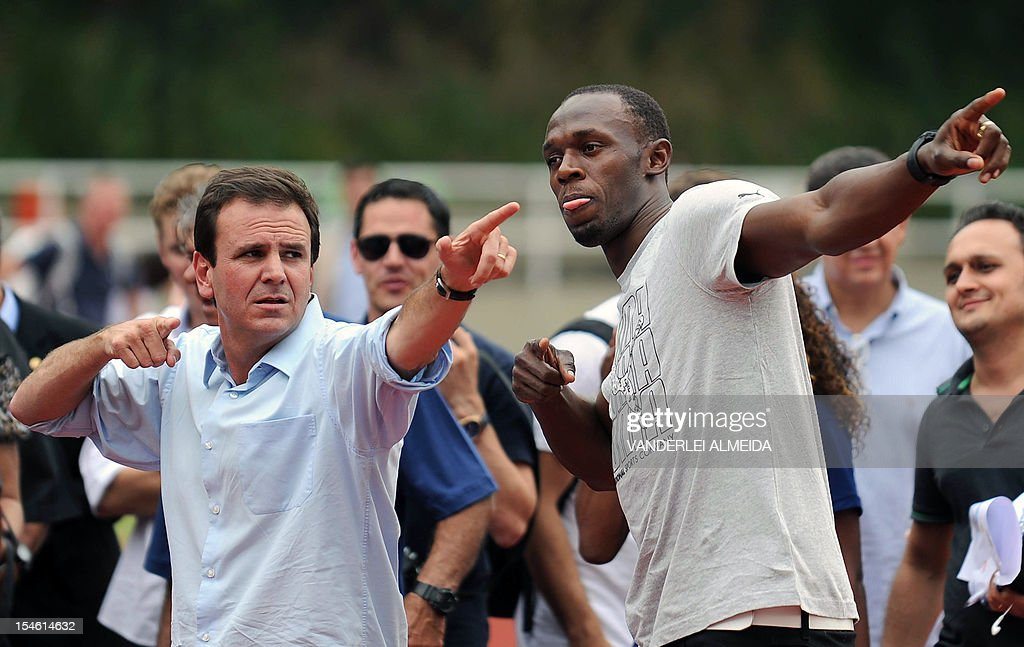 Jamaican sprinter and six-time Olympic gold medalist Usain Bolt (R) and Rio de Janeiro's Mayor Eduardo Paes gesture after racing, during a visit to an olympic village for children in the outskirts of Rio de Janeiro, on October 23, 2012.