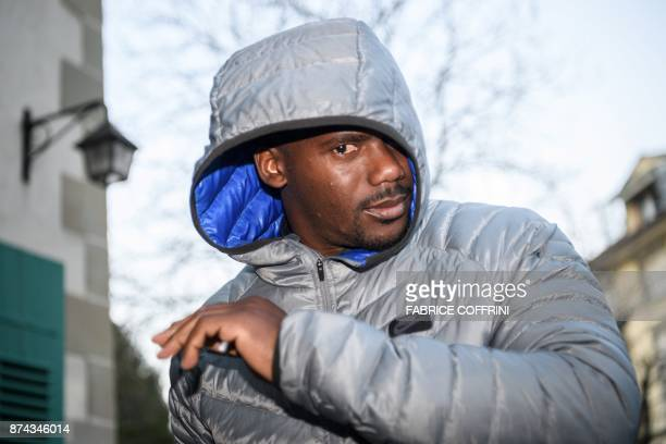 Jamaican sprinter Nesta Carter tries to hide his face from reporters upon his arrival to his appeal hearing before the Court of Arbitration for Sport...