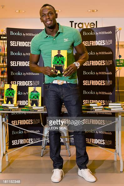 Jamaican sprinter Usain Bolt poses for photographs as he prepares to sign copies of his autobiography 'Faster than Lightning' during a photocall at...