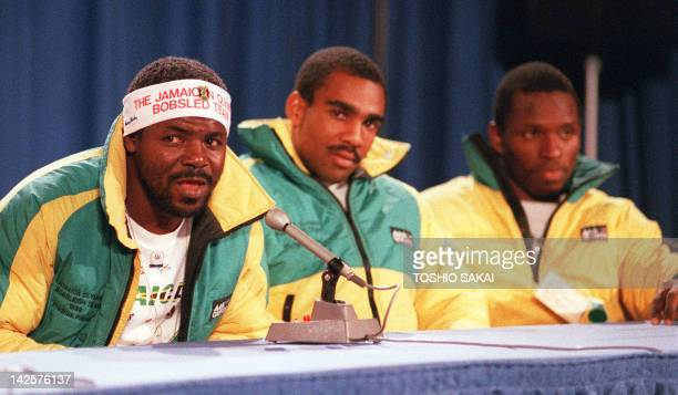 Jamaica's bobsled team member Frederick Powell speaks to newsmen during a press conference as his teammates Michael White and Allen Caswell listen 12...