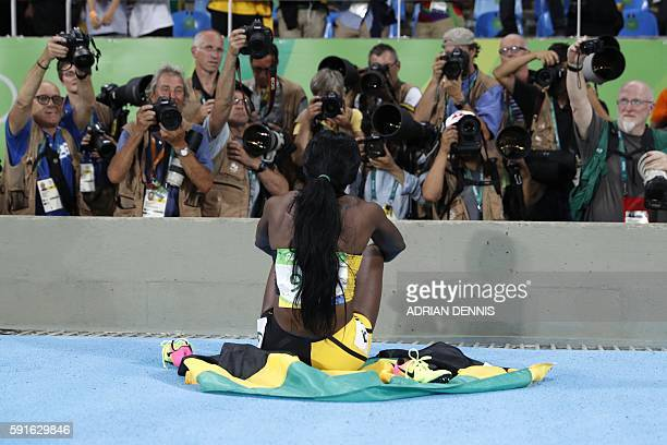Jamaica's Elaine Thompson celebrates winning the gold medal in the Women's 200m Final during the athletics event at the Rio 2016 Olympic Games at the...