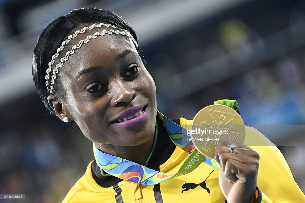 Jamaica's Elaine Thompson poses with her gold medal on the podium of the Women's 200m during the athletics event at the Rio 2016 Olympic Games at the...