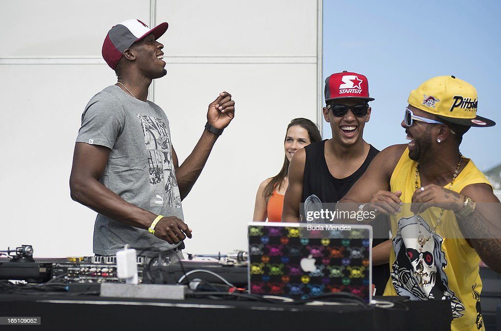 Jamaica's Olympic gold medallist Usain Bolt looks at the Djs playing music during a 'Mano a Mano' challenge at Copacabana beach on March 30, 2013 in Rio de Janeiro, Brazil.