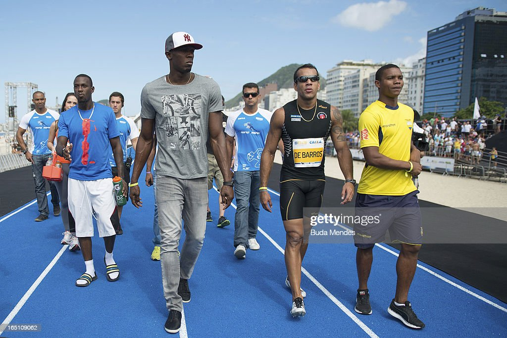 Jamaica's Olympic gold medallist Usain Bolt (2L) walk with Antigua and Barbuda's Daniel Bailey (L), (3L) Bruno Lins of Brazil and Alex Qui–ones of Ecuador on the runway during a 'Mano a Mano' challenge at Copacabana beach on March 30, 2013 in Rio de Janeiro, Brazil.