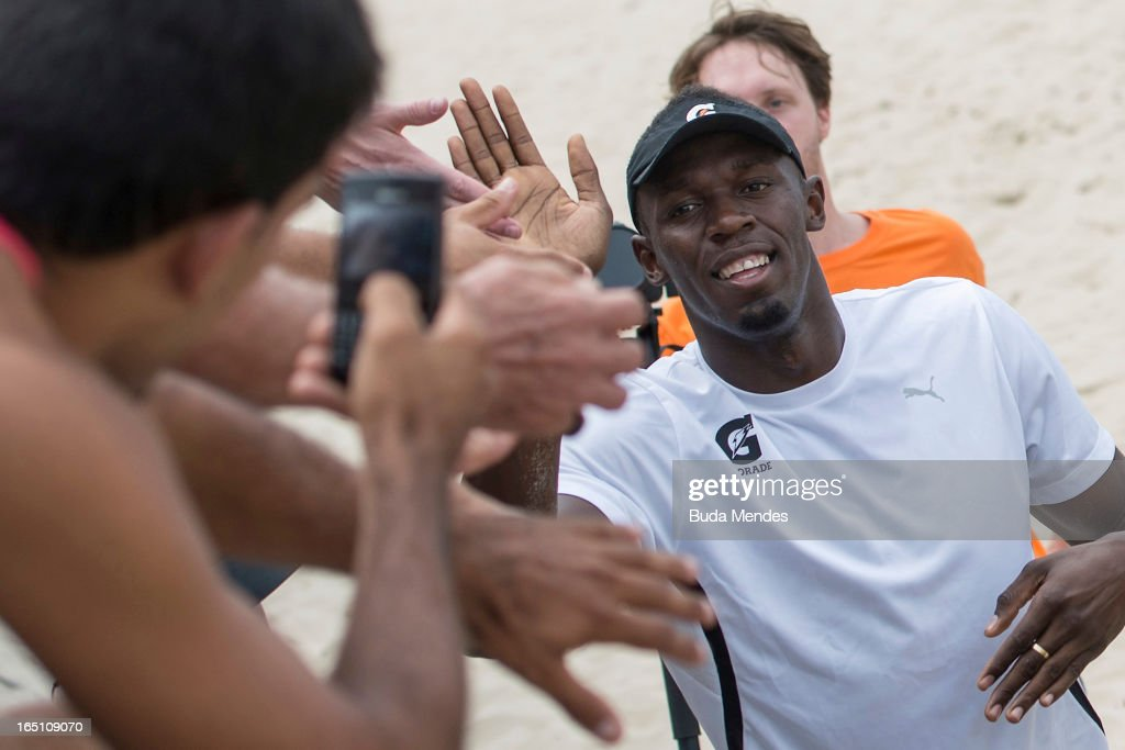 Jamaica's Olympic gold medallist Usain Bolt with fans during a 'Mano a Mano' challenge at Copacabana beach on March 30, 2013 in Rio de Janeiro, Brazil.